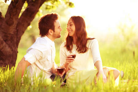 loving man and woman in the park laughing and drinking wine photo