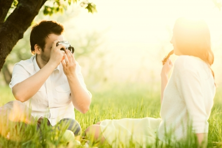 young attractive man taking photos of his girlfriend in the park photo