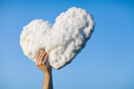 Young man get the heart - cloud to make proffer to his girlfriend from blue clear sky Stock Photo