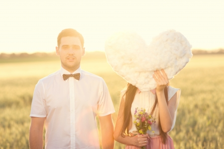 Portrait of couple in love that holdings heart - cloud in the field on sunset  Close man face