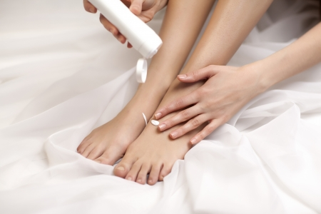 Lower section of young woman applying body lotion to her leg photo