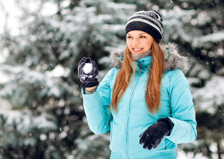 beautiful happy woman playing with snow photo