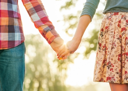 Young couple in love walking in the autumn park holding hands  Stock Photo