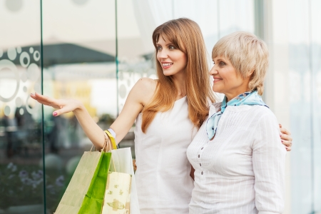 mature old generation: Adult mother and daughter after shopping on the background of the large glass windows. Stock Photo