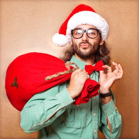 Santa Claus with a bag of gifts looking at the camera and holding his bow tie Stock Photo - 23446499
