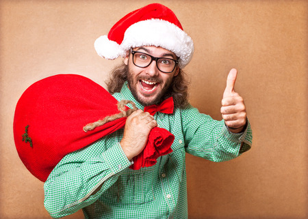 Santa Claus with a bag of gifts looking at camera and showing sign of cool Stock Photo - 23446500
