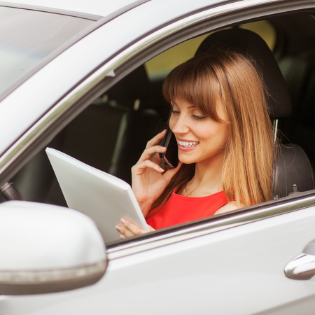 business travel: busy businesswoman with document and laptop in car photo