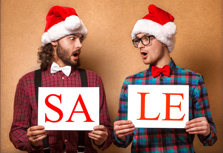 Christmas, x-mas, people, advertisement, sale concept - happy two man in santa helper hat with blank white board. Hipster style. photo