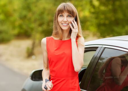 Young business woman calling on the phone against a city traffic photo