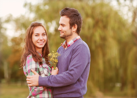 Young couple in love walking in the autumn park near the river. photo