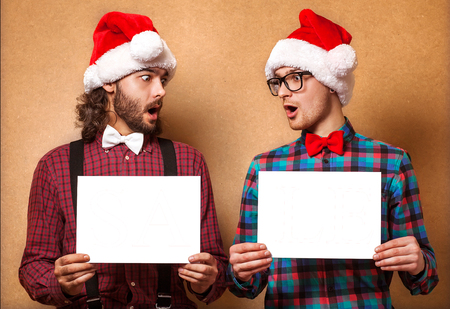 Christmas, x-mas, people, advertisement, sale concept - happy two man in santa helper hat with blank white board  Hipster style  photo