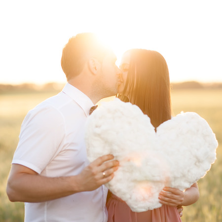 Young couple kissing behind heart cutout in the nature