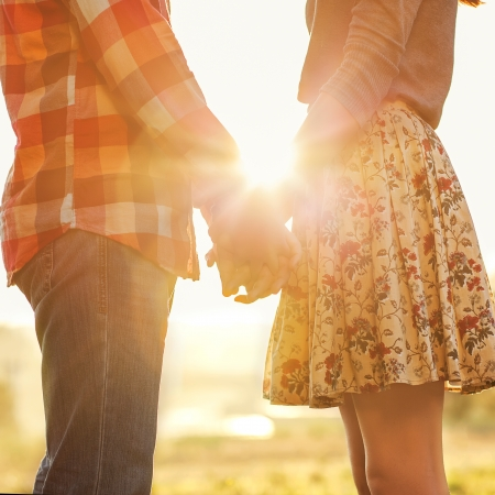 married couple: Young couple in love walking in the autumn park holding hands looking in the sunset