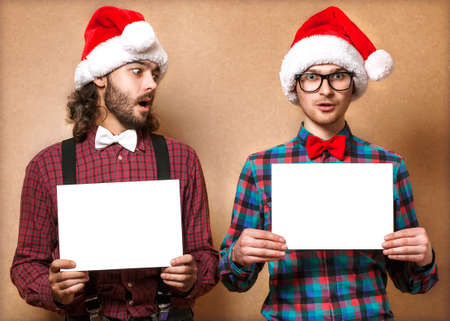 Christmas, x-mas, people, advertisement, sale concept - happy two man in santa helper hat with blank white board  Hipster style Stock Photo - 24258058
