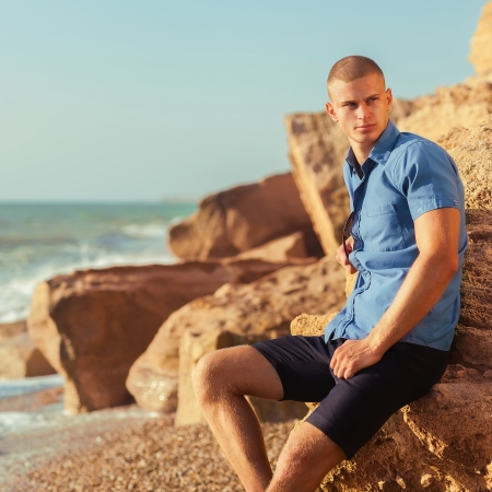 Portrait of a handsome young muscular man in swim trunks with water ocean  Stock Photo