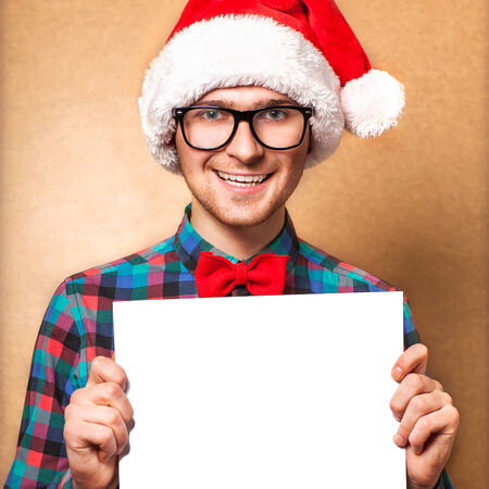 Hipster Santa Claus pointing in white blank sign with smile, isolated on background photo