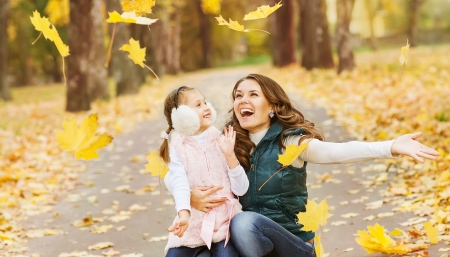 Mother and daughter having fun in the autumn park among the falling leaves. photo