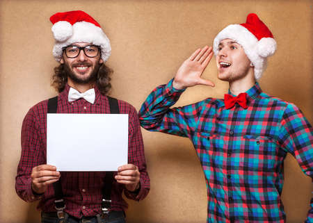Christmas, x-mas, people, advertisement, sale concept - happy two man in santa helper hat with blank white board. Hipster style. Stock Photo - 24258085