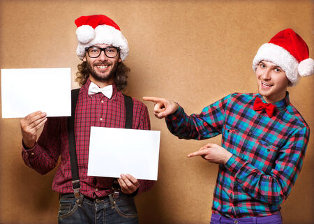 Christmas, x-mas, people, advertisement, sale concept - happy two man in santa helper hat with blank white board. Hipster style. Stock Photo - 24258086