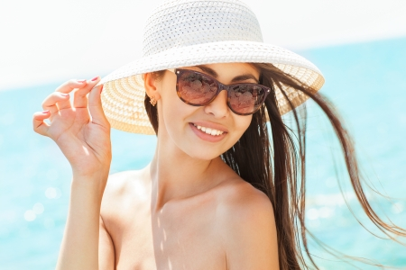 Young beautiful woman on the beach, wearing a hat 版權商用圖片