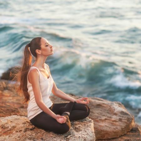 girl in lotus pose at sunset Standard-Bild