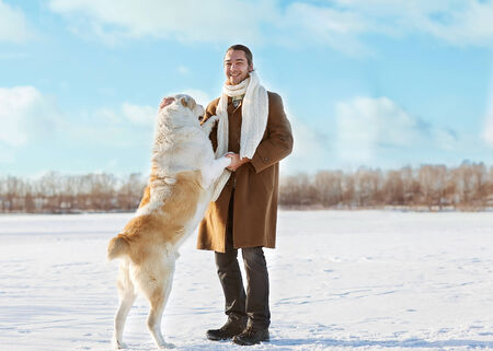 Man and central Asian shepherd walk in the lake photo