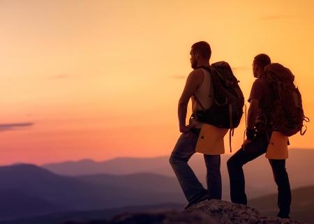Two hikers enjoying sunrise from top of a mountain Foto de archivo