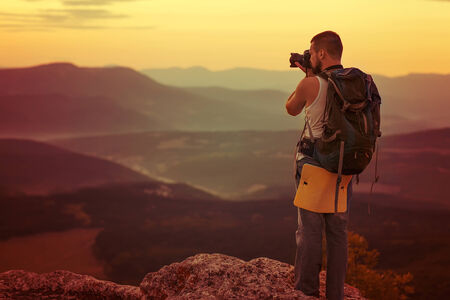 human photography: Nature photographer taking photos in the mountains Stock Photo