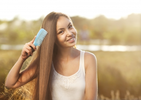 light brown hair: beautiful girl combs her hair Asian appearance  Stock Photo