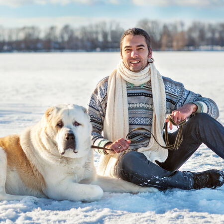 Man and central Asian shepherd playing with his dog outdoors photo