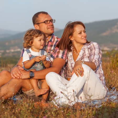 Happy mother, father and daughter in sunset Stock Photo
