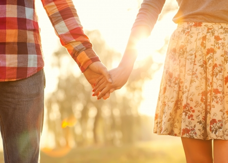 Young couple in love walking in the autumn park holding hands looking in the sunset Stock Photo - 25321725