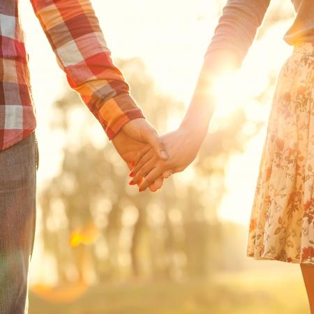 pareja de esposos: Pareja joven en el amor que recorre en el parque del otoño de la mano en busca de la puesta de sol