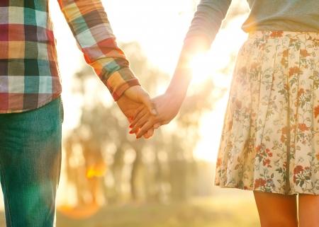 Jong paar in liefde wandelen in het najaar park hand in hand op zoek in de zonsondergang