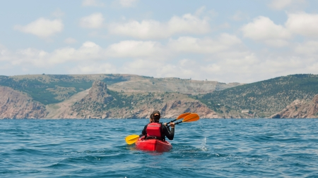 traveler kayaking in the thai ocean from backward view photo