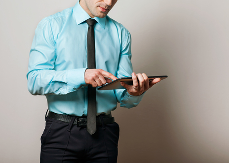Serious young male executive using digital tablet against gray background photo