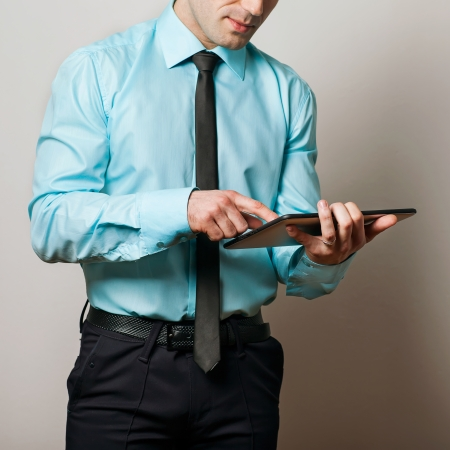 Serious young male executive using digital tablet against gray background Stock Photo