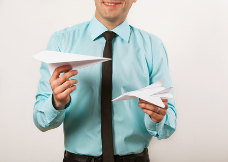 young male businessman holding origami airplanes, studio photo
