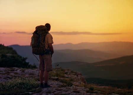 guy in the mountains at sunset. the concept of freedom Stock Photo