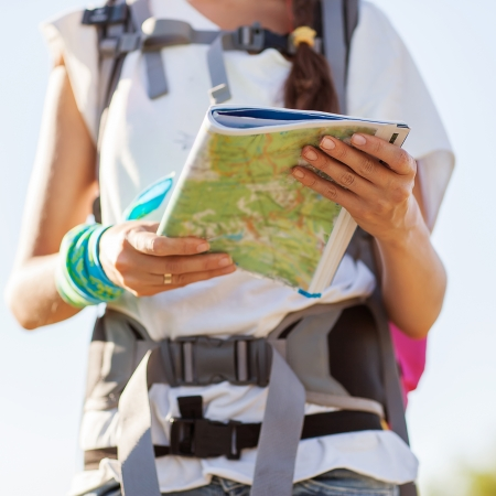 tour guide: Beautiful tourist woman on vacation with a city map with the sea and sky in the background