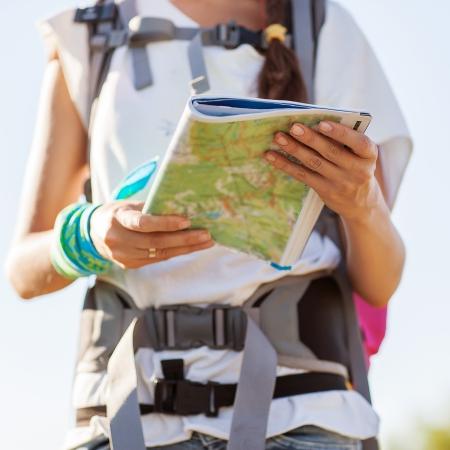 guia de turismo: Hermosa mujer turista en vacaciones con un mapa de la ciudad con el mar y el cielo en el fondo Foto de archivo