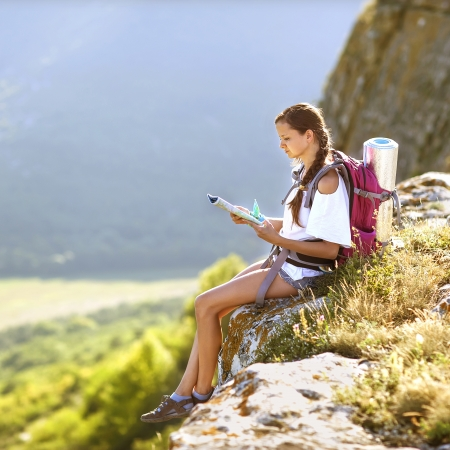 Young, beautiful girl with a backpack on her back, studying a map while standing on the plateau. In the background, green meadows and majestic mountains. Foto de archivo
