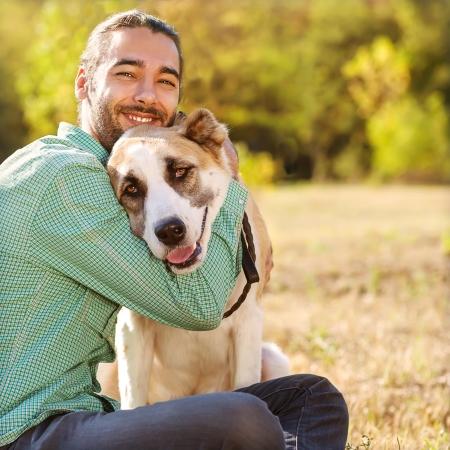 dog on leash: El hombre y la caminata de pastor asi�tico central en el parque. �l mantiene el perro en la correa. Foto de archivo