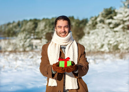man with gift waiting his woman in the woods in winter the romantic, valentines day concept photo