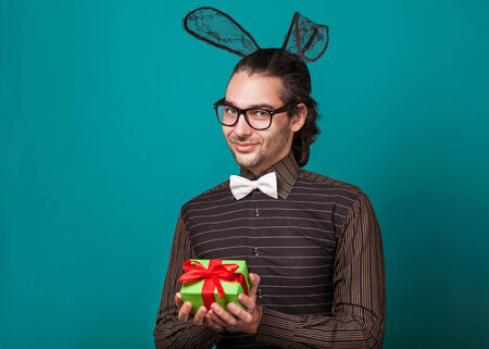 Fashion guy in bunny ears of holding gift  valentine photo