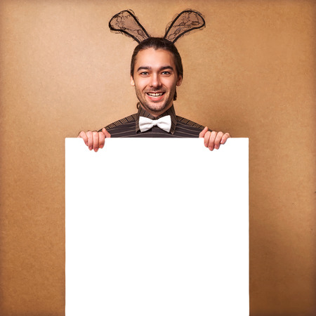 Fashion guy in  bunny with rabbit ears holding white board  Sale, prices fall photo
