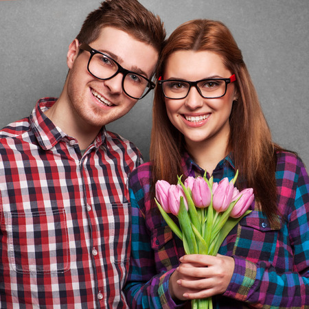 Young couple in love make a heart and hands are holding a bouquet of tulips  The concept of Valentine photo