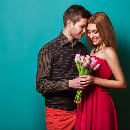 nude sexy girl: Portrait of young couple in love with flowers tulips posing at studio dressed in classic clothes