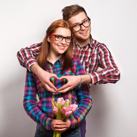 Young couple in love make a heart and hands are holding a bouquet of tulips. The concept of Valentines Day
