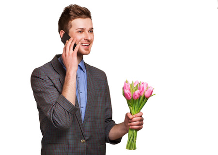 suitor: A young romantic man holding a bouquet of flowers and talking on the phone isolated on white